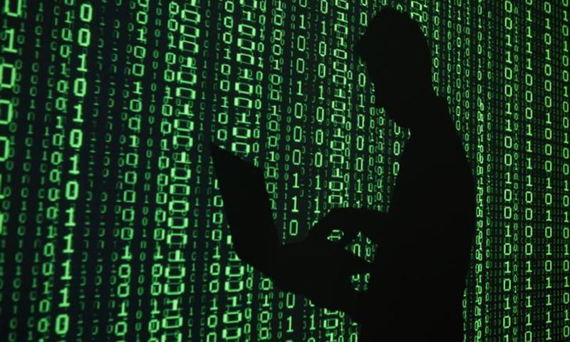 An illustration picture shows a projection of binary code around the shadow of a man holding a laptop computer in an office in Warsaw
